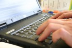 Hands writing in a laptop
